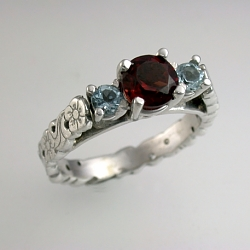 14kt white gold sculpted floral engagement ring set with a 5mm ruby and two 3mm side aquamarine.