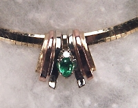 Tri-color gold slide with .70ct oval emerald and .15ct diamond