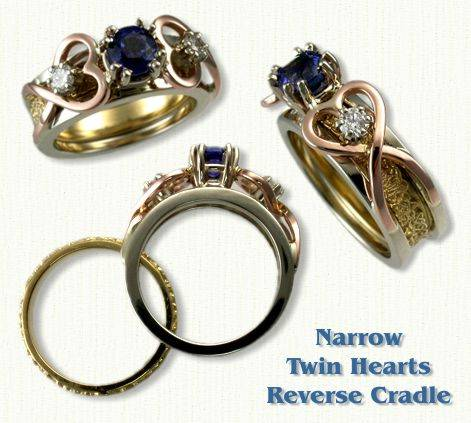 Twin Heart Reverse Cradle set with a round blue sapphire and two side diamonds. Shown in 14kt White Rails, Yellow Triangle Heart Knot Inside Band, and Rose Gold Hearts.